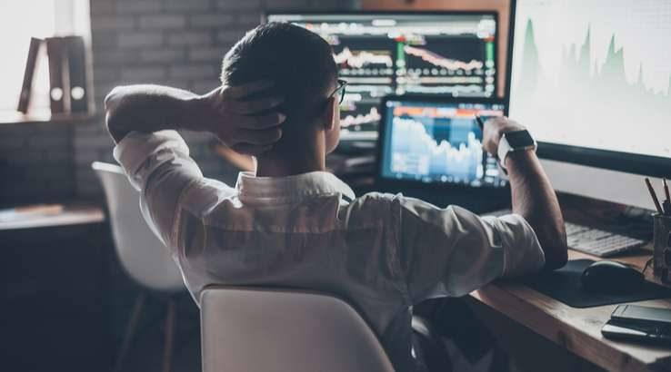 Man sitting at computer looking at trading charts.